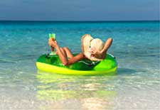 Woman lounging on intertube with beverage in the ocean